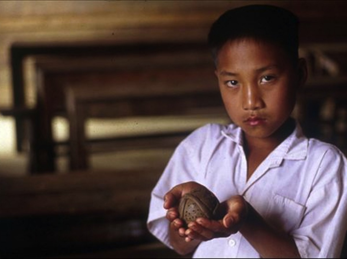 Young boy holding an unexploded cluster bomb in his out-stretched arms