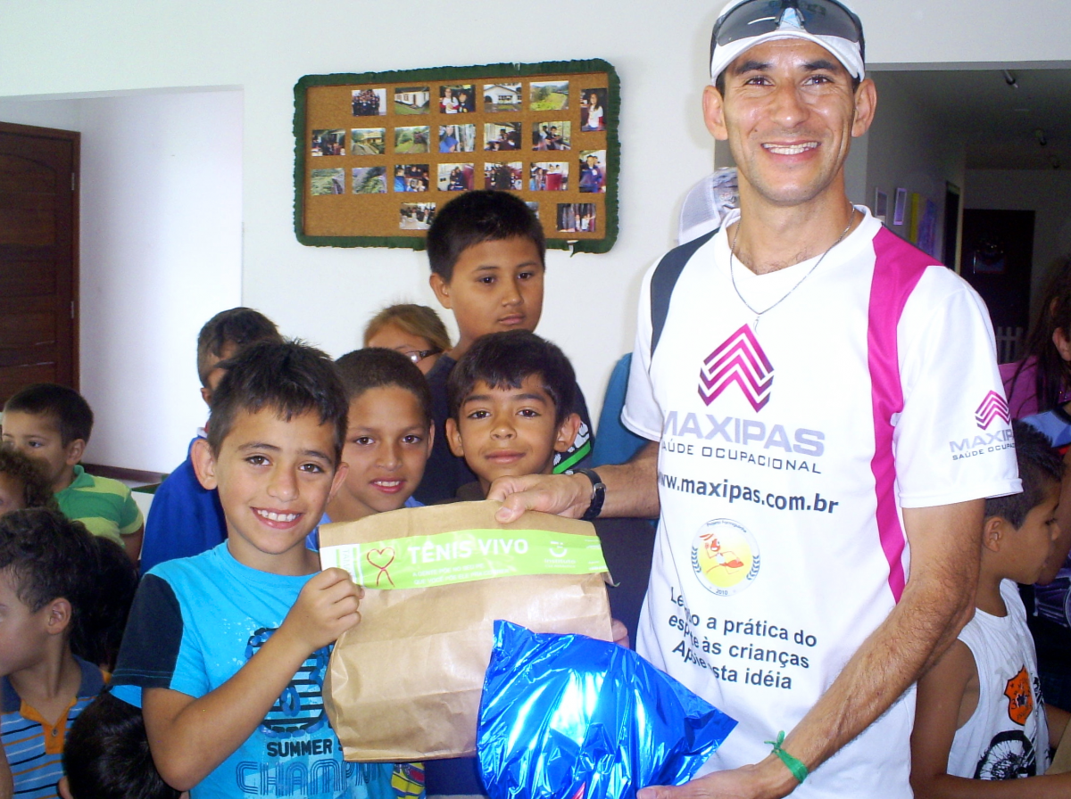 Young smiling children receive running shoes from a staff member of Cia Athletica gyms Brazil