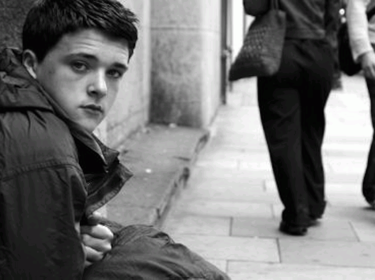 Homeless young boy living rough on street