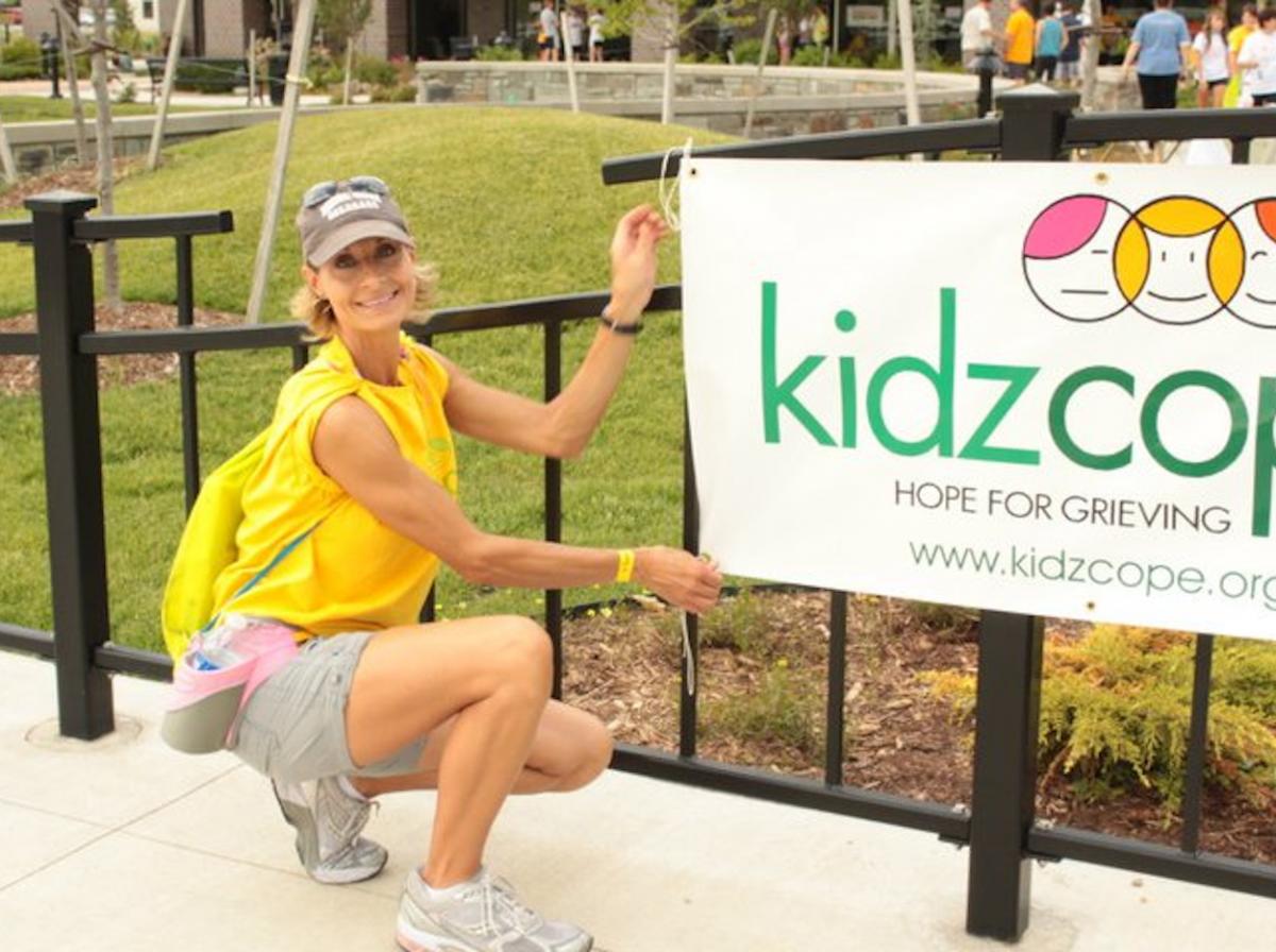 Women kneeling next to Kidzcope charity banner