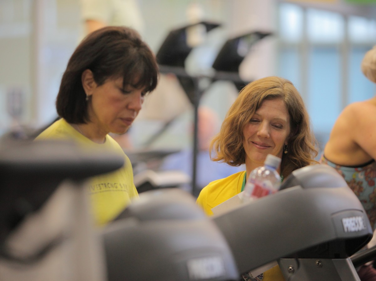 Two women wearing Livestrong t-shirts exercising on treadmill