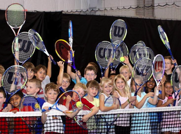 Group of children standing on tennis court while attending Genesis Foundation for Fitness & Tennis