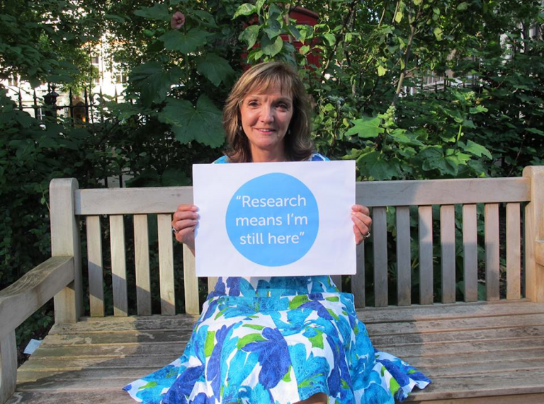 Women in blue dress holding a sign saying 'Research means I am still here' - Cancer Research UK