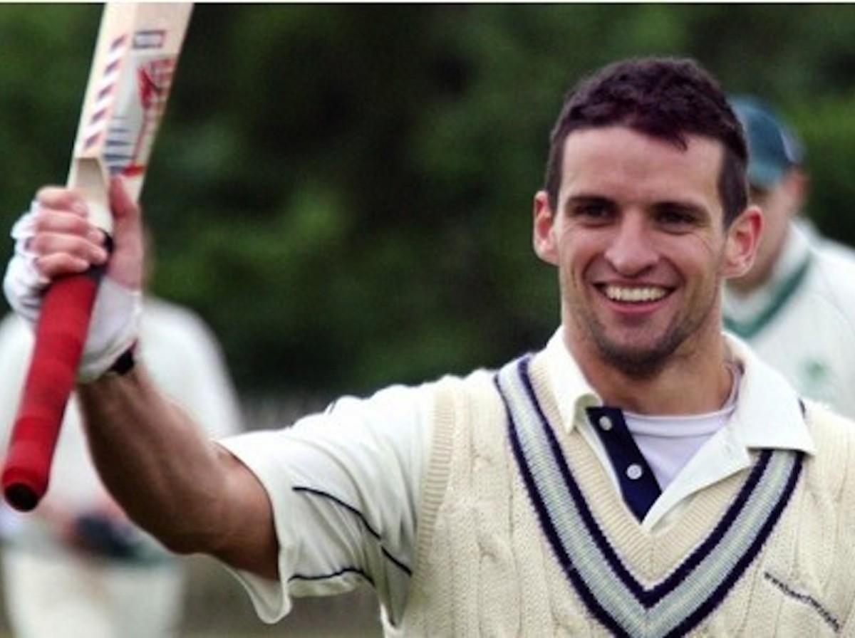 David Smyth in cricket whites and holding his cricket bat