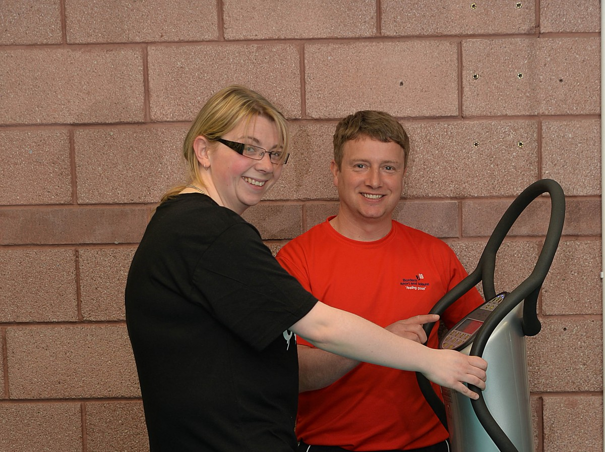 Borders Sport and Leisure gym employee advising Multiple Sclerosis sufferer how to use Power Plate vibration training machine