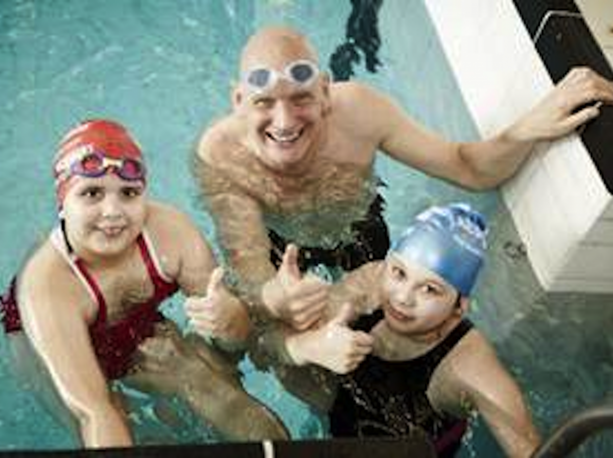 Duncan Goodhew President of Swimathon in a swimming pool with two young fund raisers