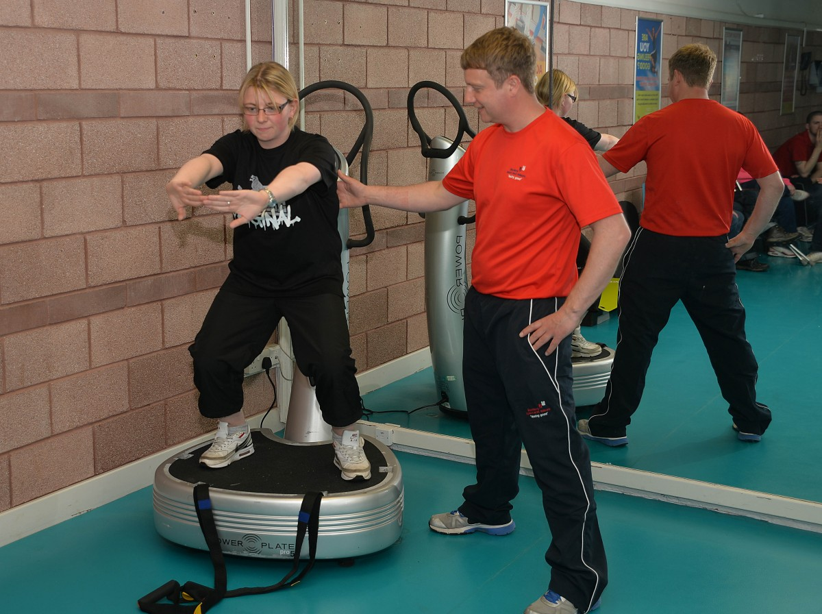Borders Sport and Leisure gym employee giving instruction to customer living with Multiple Sclerosis