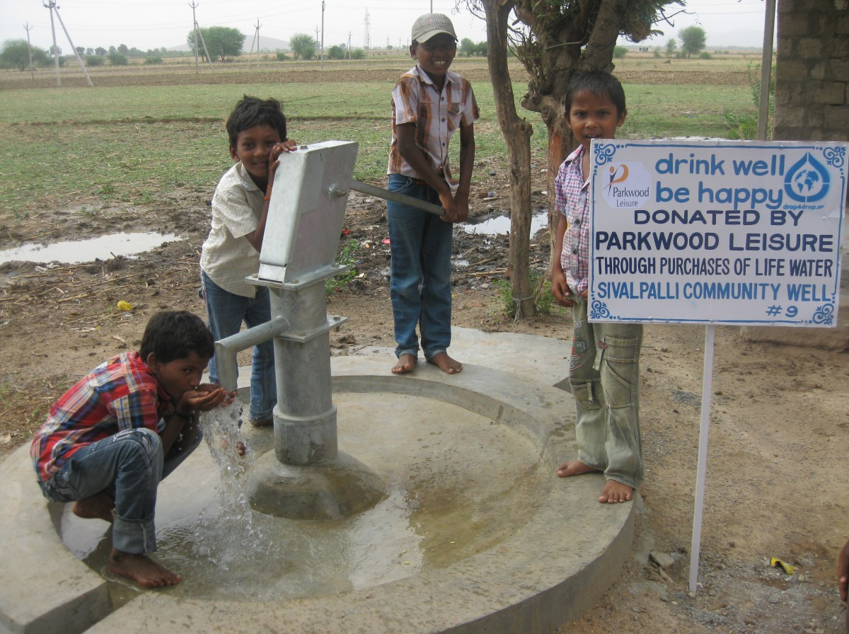 Smiling children sitting alongside their new fresh water well in Sivalpalli India
