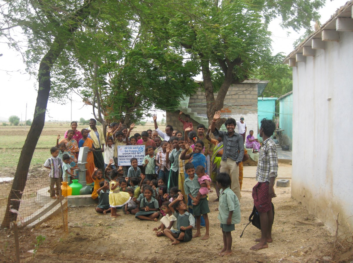 Smiling children and adults sitting alongside their new fresh water well