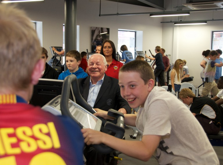 Dave Whelan, one of the Founders of Wigan Youth Zone tries out new Technogym equipment along with group of young people