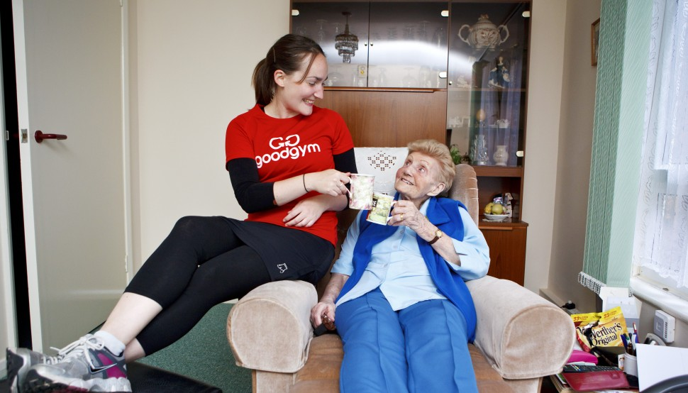 Female GoodGym runner drinking tea with an elderly women