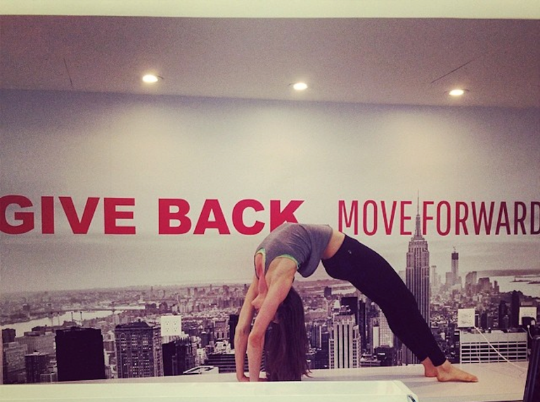Internal picture of The Movement Studio in New York with a slogan on the wall: Give Back, Move Forward