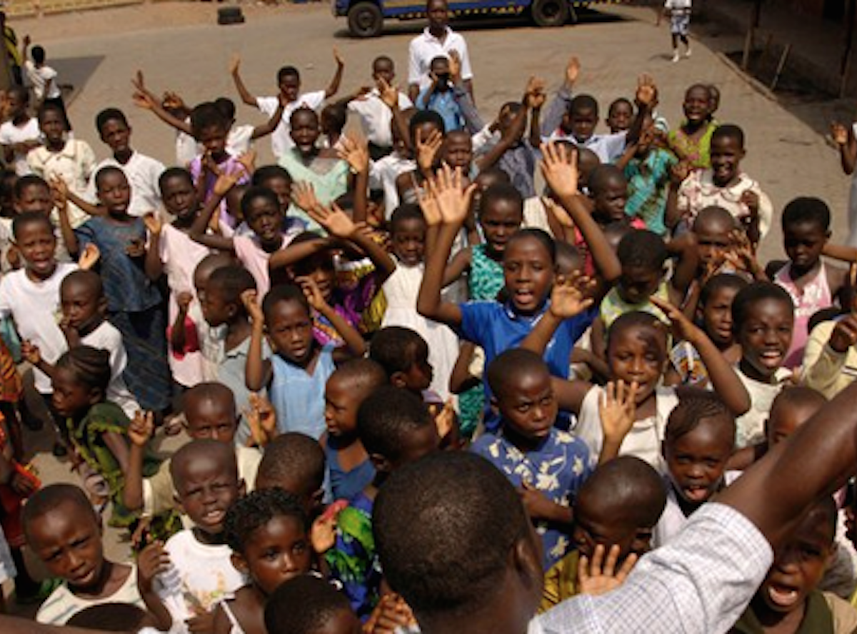Large group of young Ugandan children raising their hands and smiling. They are supported by the charity, Compassion