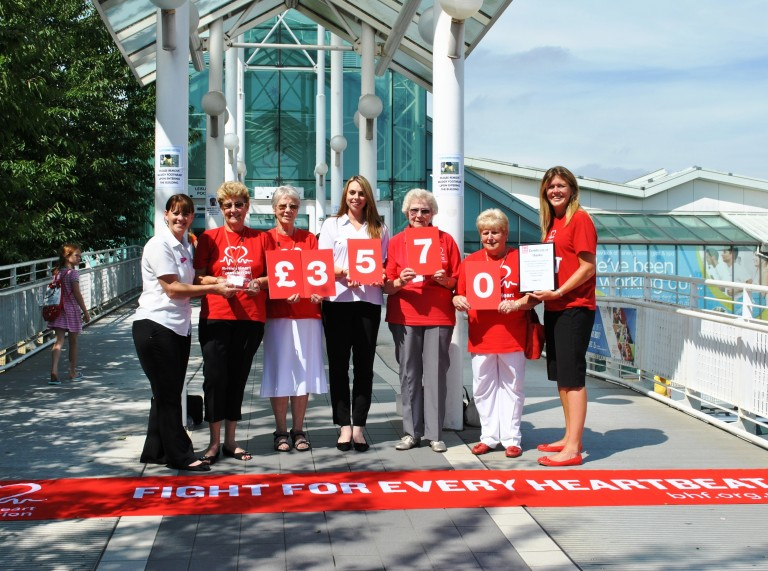 Seven staff members from Freedom Leisure holding a sign confirming £3,570 raised for the British Heart Foundation