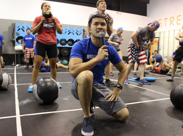 Man holding microphone and urging people to workout harder during Workout for Warriers fund raiser