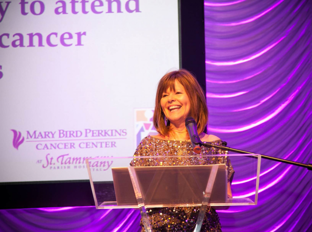Franco's staff member (Patti) speaking on stage at the Francos fund raising Mary Bird Perkins Cancer Center event