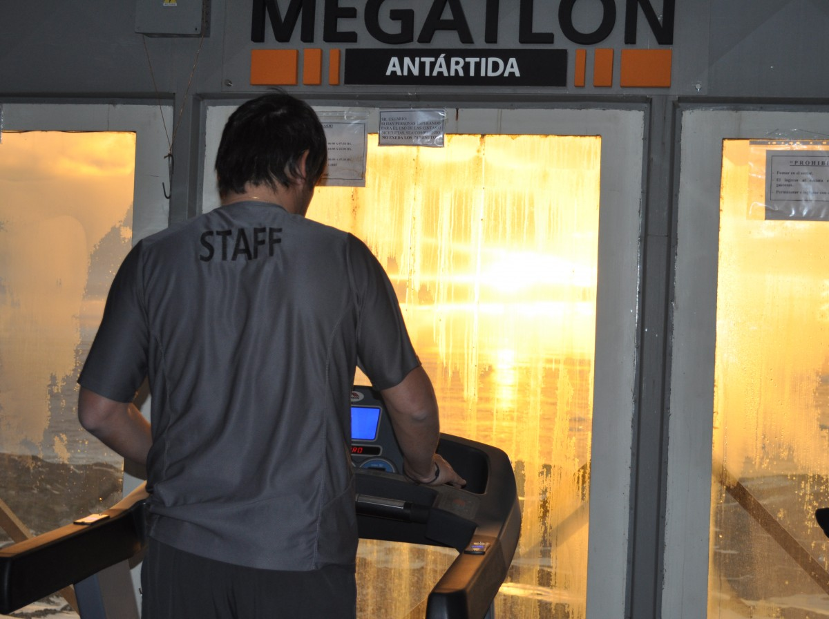 Man exercising on the treadmill at the Megatlon gym, Marambio Base, Antarctica. He has am amazing view of the sun setting over Antarctica.