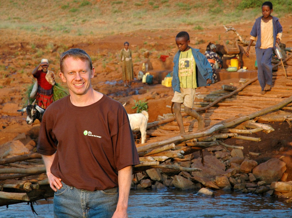 Darren Kanwischer owner of Fifth Avenue Club in Calgary, Alberta standing next to a new water well in the Belo region of Ethiopia - Gymtopia.org