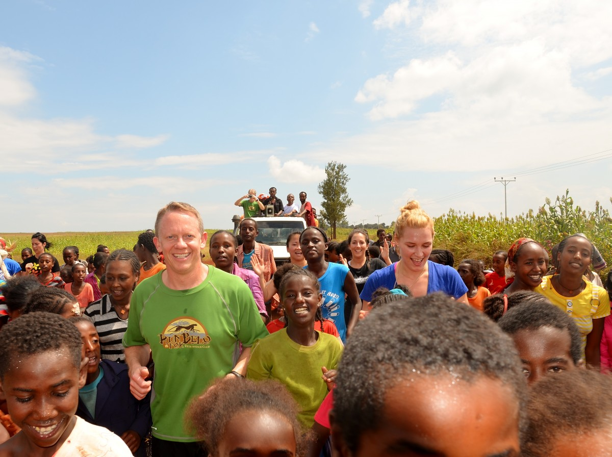 Darren Kanwischer owner of Fifth Avenue Club Calgary taking part in a community run on a visit to the Belo region Ethiopia. The run has both children and adults who are smiling at the camera – Gymtopia.org