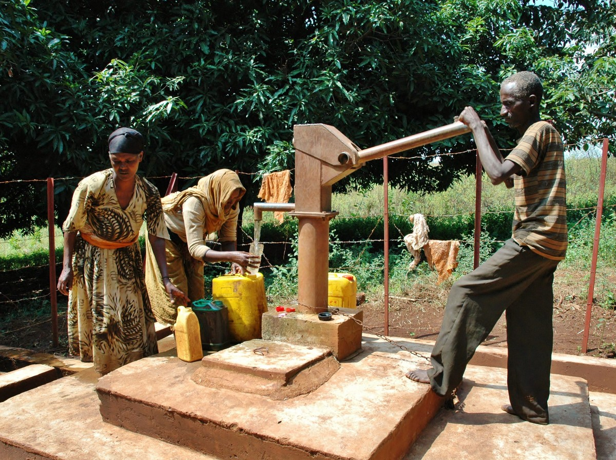 A man and and two women are pumping water from a new well constructed in the Belo region of Ethiopia. The clean water is being pumped into platic yellow jerry can – Gymtopia.org