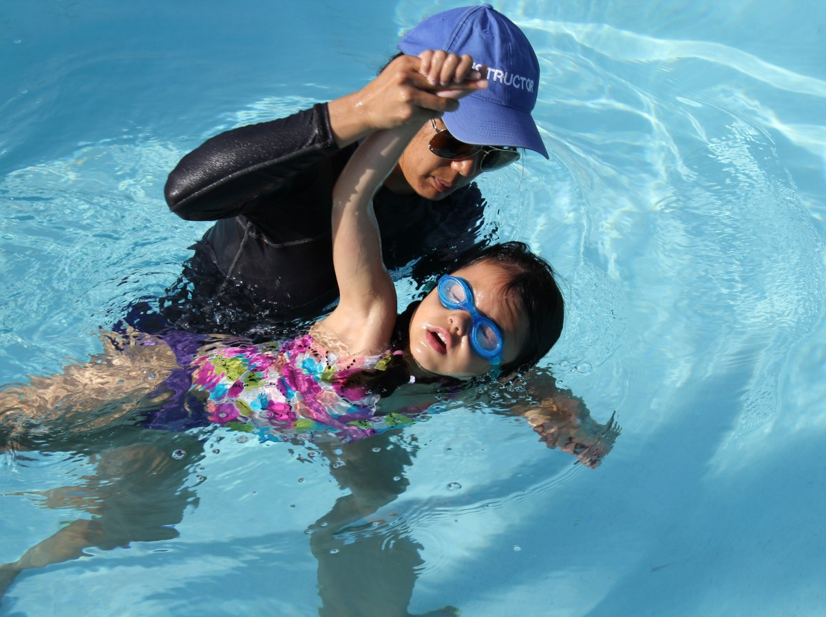 Swimming Instructor from The Claremont Club supporting a young girl in the club outdoor pool