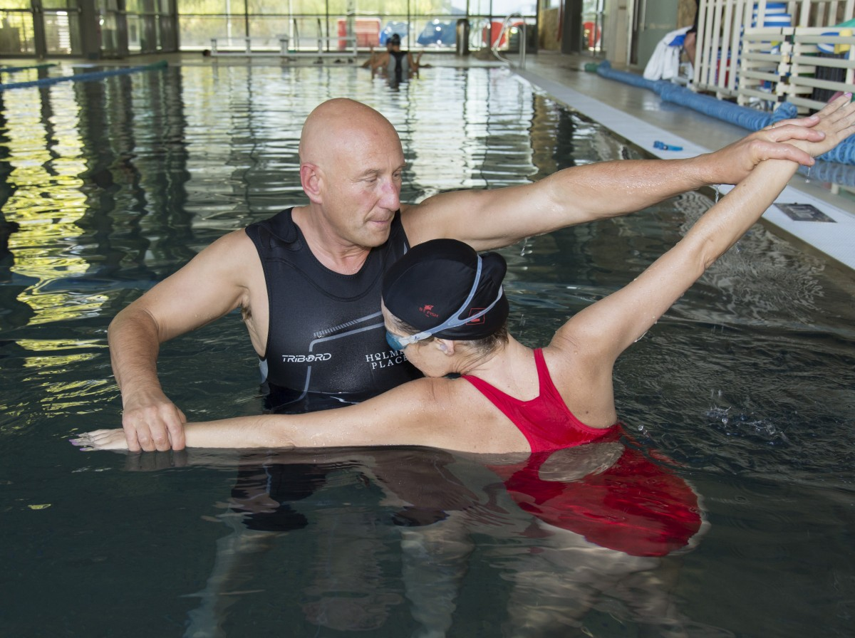 A male Holmes Place swimming instructor in the pool helping a female member with her swimming technique