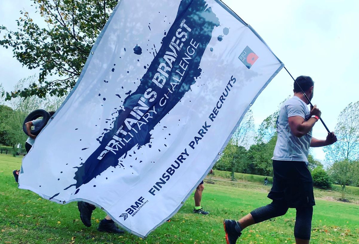 "Man running in Finsbury Park London with a BMF banner which says ""Britain's Bravest Military Challenge"" which refers to supporting the Royal British Legion Industries (RBLI)"